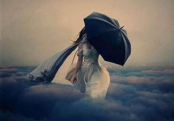 nainen kävelee pilvissä sateenvarjon kanssa