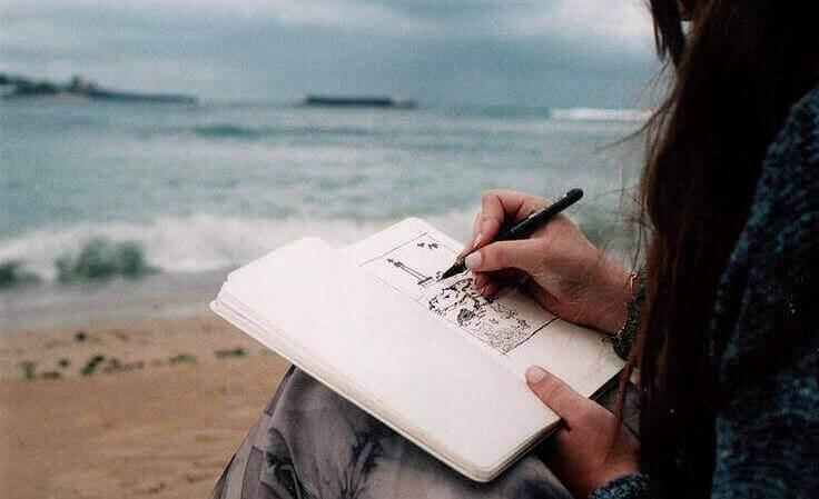 nainen piirtää rannalla