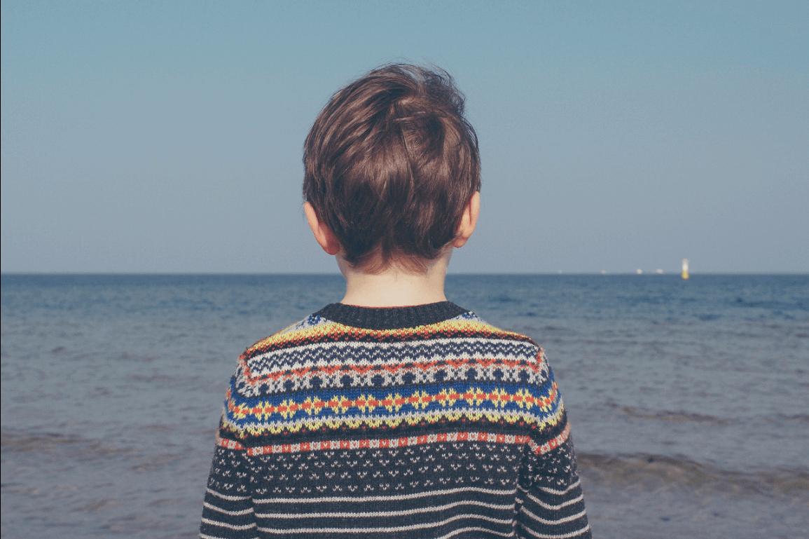 Poika seisoo rannalla yksin