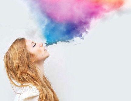 nainen puhaltaa värejä