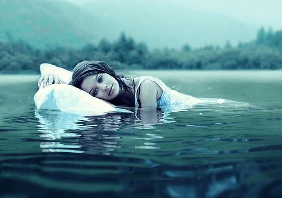 nainen kelluu vedessä tyynyn kanssa