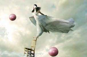 nainen seisoo tuolin päällä ilmassa