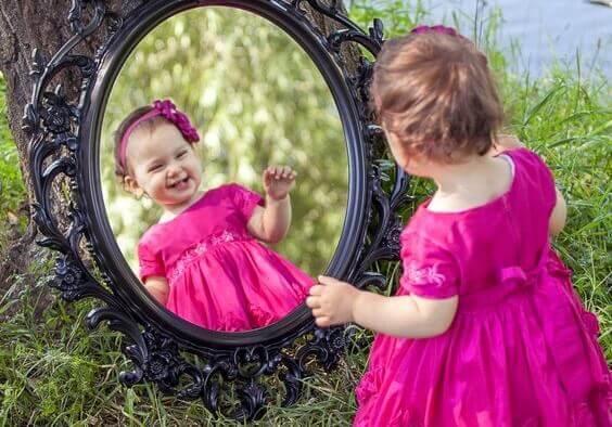 Itseään peilistä katseleva pikkutyttö