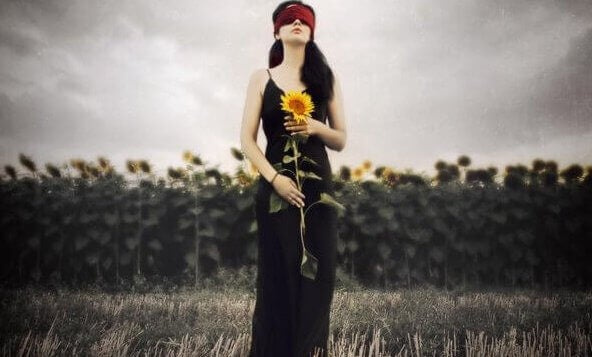naisella auringonkukka ja side silmillä