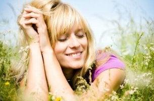 nainen hymyilee pellolla