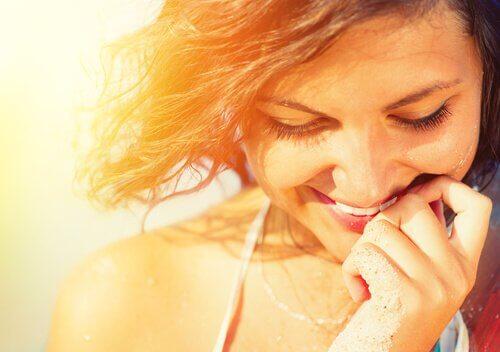 Auringon valossa hymyilevä nainen