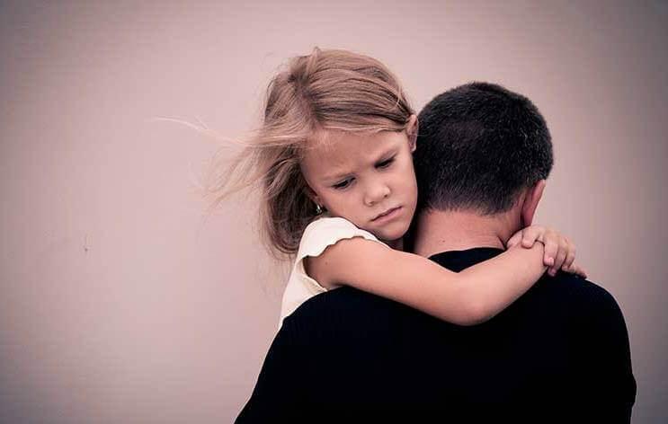 Tyytymätön tyttö isän sylissä