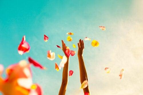 kädet heittelevät kukkien terälehtiä ilmaan