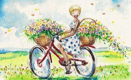 nainen pyöräilee kukkien kanssa