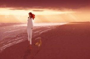 nainen kävelee rannalla