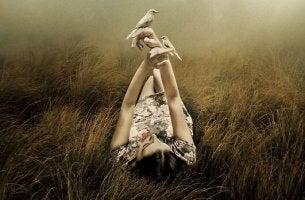 naisella on kädessä lintu
