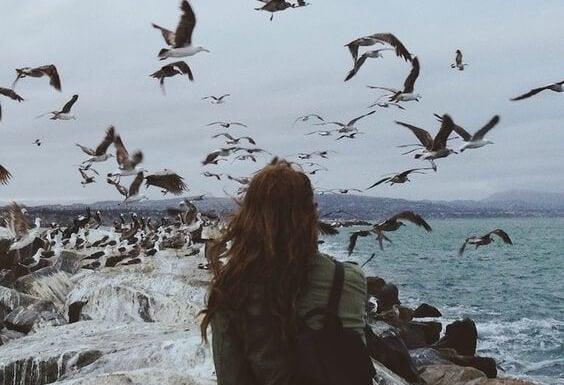Nainen lokkien ympäröimänä meren rannalla