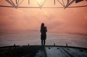 nainen katsoo tyynelle merelle
