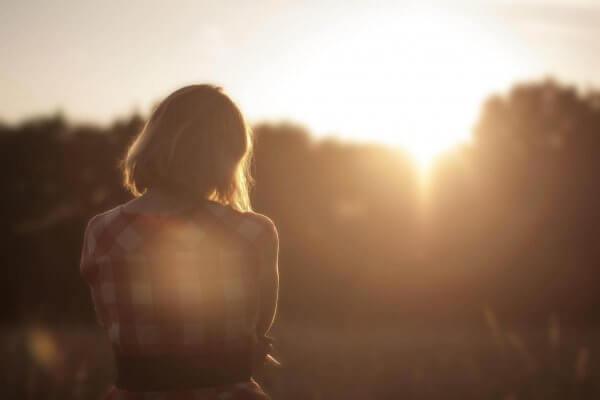 nainen yksin auringonnousussa