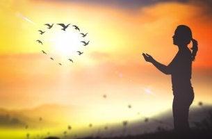 nainen meditoi ja linnut lentävät