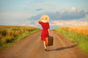 nainen ja matkalaukku tiellä