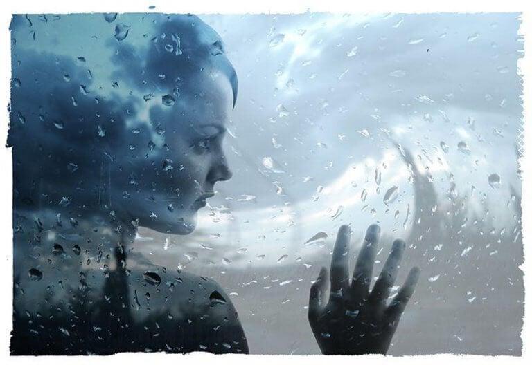 tyttö sateisen ikkunan takana