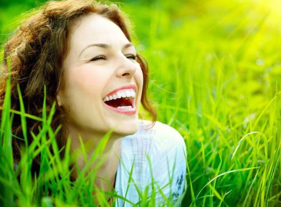 nainen nauraa nurmikolla