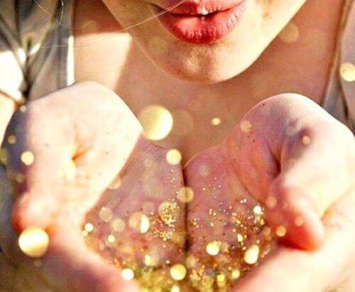 nainen puhaltaa kultahileitä