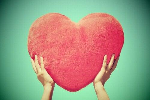 kädet pitelevät sydäntyynyä