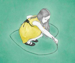 tyttö piirtää maahan sydämen