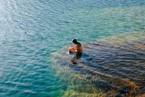 nainen kiven päällä vedessä