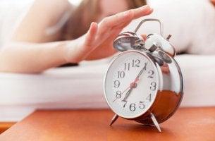 Käsi tavoittelee herätyskelloa