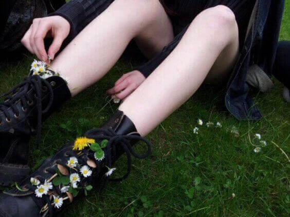 teini laittaa kukkia saappaisiinsa