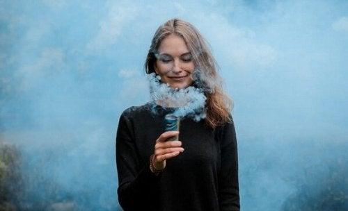 nainen hengittää savua