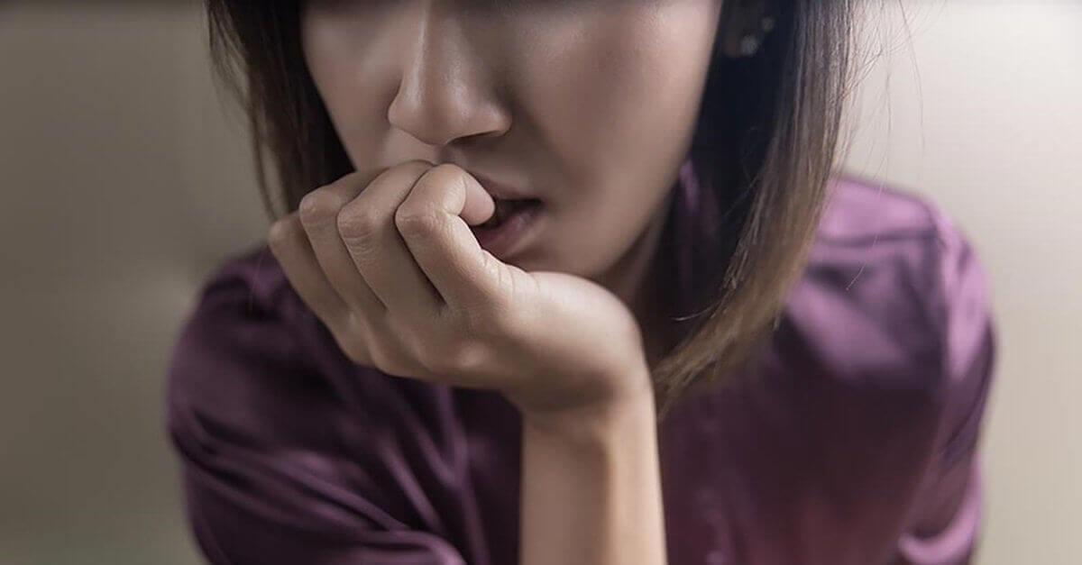 ahdistunut nainen puree kynsiään