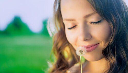 nainen haistelee tai puhaltelee kukan