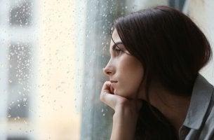 nainen katsoo ulos sateeseen