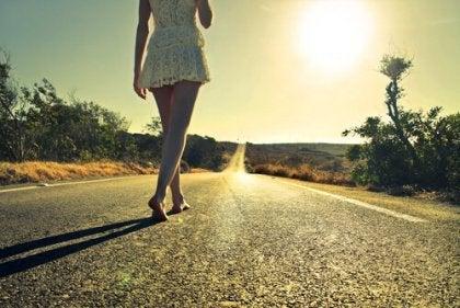 nainen kävelee maantiellä paljain jaloin