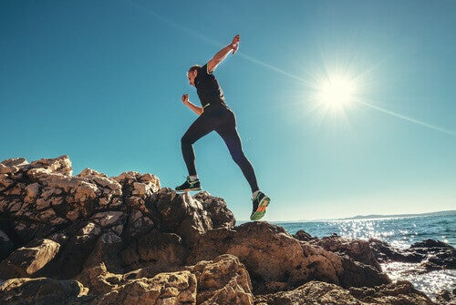 nainen juoksee rantakivissä