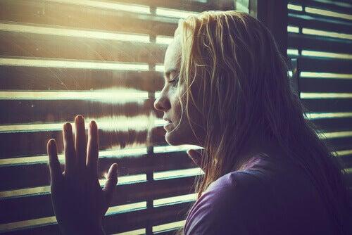 nainen katselee ikkunan läpi
