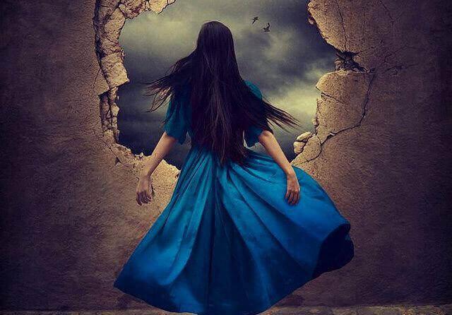 nainen rikkinäisen seinän edessä