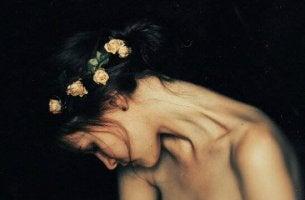 surullisella naisella kukkia päässään
