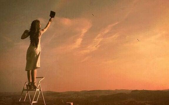 nainen maalaa taivasta