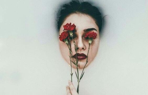 naisella kukkia kasvojen edessä