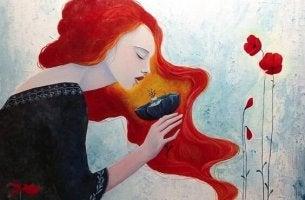 punatukkainen nainen haistelee kukkaa