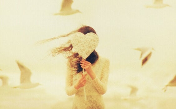 tyttö piilottelee sydämen takana