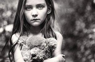 surullinen tyttö halaa nalleaan