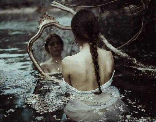 tyttö vedessä katsoo itseään peilistä
