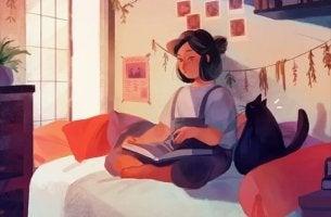 tyttö lukee sängyssä kissan kanssa