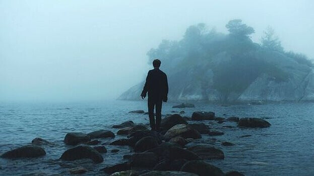 mies kävelee kivien päällä vedessä