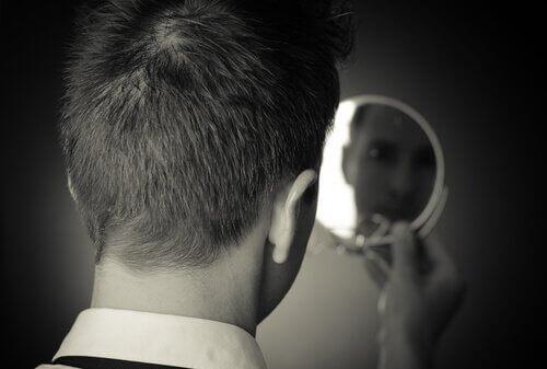mies katsoo itseään peilistä