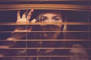nainen kurkistaa ulos ikkunasta