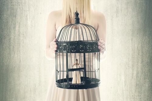 nainen pitelee itseään häkissä