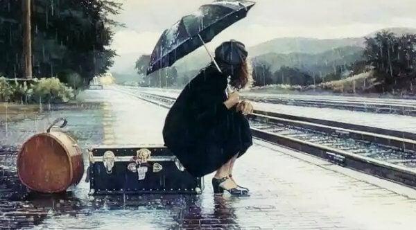 nainen odottaa junaa sateessa