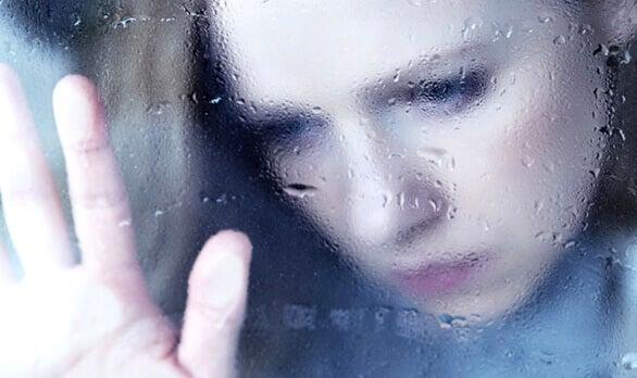 tyttö märän ikkunan takana